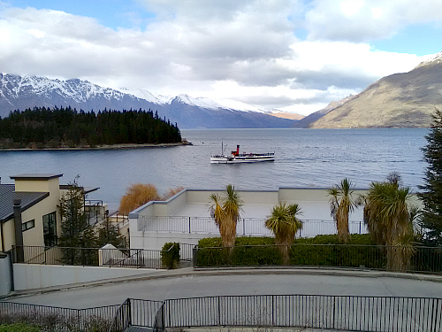 The TSS Earnslaw cruises past Pepper's Beacon apartments in Queenstown