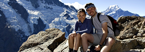 Hiking New Zealand couple sitting on rocks in alps