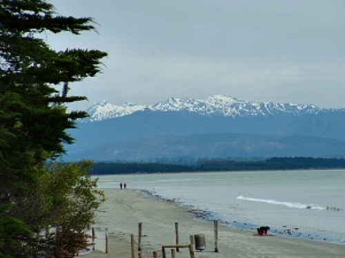 Looking across Tahunanui beach, Nelson, towards snow capped peaks