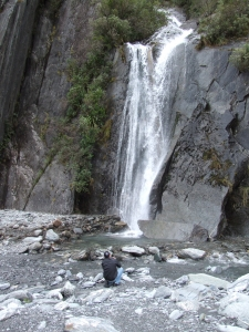 Tim at a waterfall on the walk to the terminal face of Franz Josef Glacier