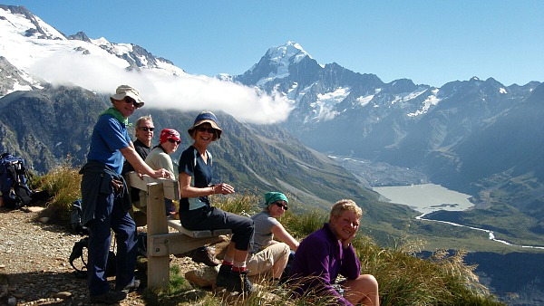 Hiking New Zealand trekkers resting above valley