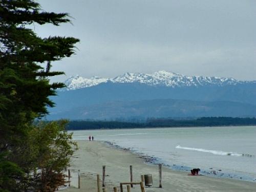 Looking across Tahunanui beach, Nelson, towards snow capped peaks